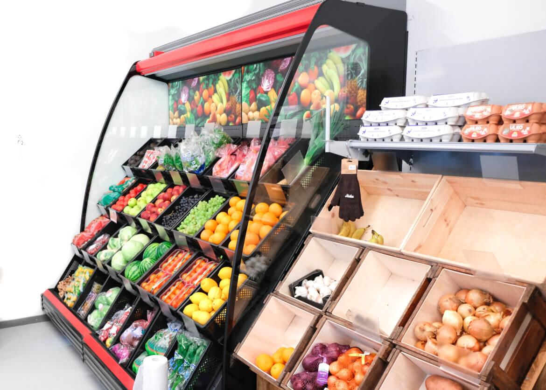Harmaa HeVi -kylmäkaluste, jossa punaiset etuosat. Lokerot hedelmiä ja vihanneksia varten. Vuolenkosken Kyläkauppa.